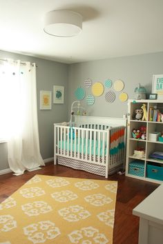 "What a fun and simple way to add color and pattern to a nursery-- put patterned fabric in needlepoint circles to create different size ""polka dots"" above the crib! Love it!!"