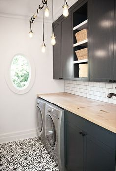 Laundry room with style / black cabinetry with industrial style pendant lighting and graphic black and white flooring