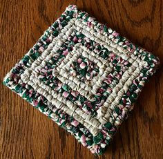 This Mug Rug is made from a variety of textiles and measures 5-1/8 x 5-3/8.