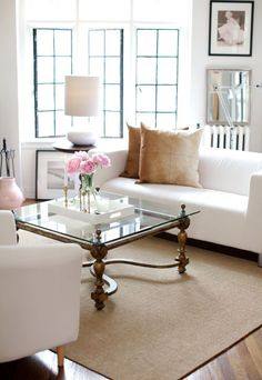 Plush Palate: windows, neutral palette, jute/grass rug over hardwood floors, glass coffee table, artwork placement