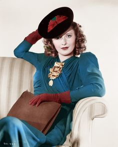 Barbara Stanwyck--look at that brooch! 40s fashion color photo print ad movie star model teal blue dress day hat gloves purse necklace hair style red brown