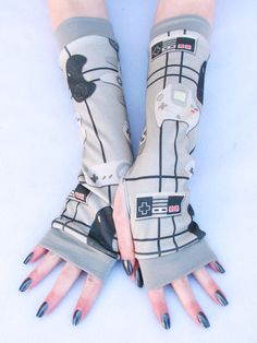 Old School Video Game Arm Warmers Sega NES. Video Game Controller Arm Warmers with Old School Video Game Controllers from pre-2000. Find your favorite: NES, Nintendo, Dreamcast, Sega, Super Nintendo controllers. For Men or Women, Unisex sizes of arm warmers. Rock your Video Game Geek status in a great design by Artist Jaana. A fantastic print of gaming controllers in gray, red and black. A great gift for a Gamer on your Holiday gift list. I love her fan artwork. She can be found on...