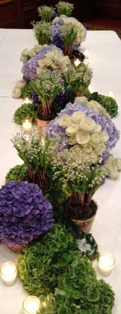 Lush & Beautiful purple & green flowers and candles table runner. Garden hydrangeas, potted lilies of the valley and perfect store bought roses. Gorgeous and affordable!