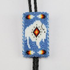 """Navajo artist Charlene Jackson made this marvelous bolo tie. The detail in this bolo tie is amazing. Great design depicting a buffalo and feathers. Backed with a soft leather. 1 3/8"""" wide x 2 1/2"""" long 43″ long with bolo strap & tips Artist card included"""