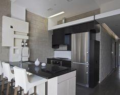 Cozinha com moveis em madeira preta e parede em bloco de concreto