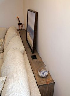 "Narrow storage behind the sofa. Make with 1×4"" lumber, hinged end panel. Love including the electrical outlet on top!"