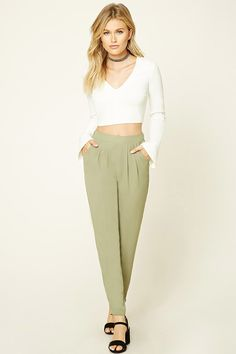 A pair of lightweight crepe woven pants featuring a pleated front, tapered leg, slanted onseam pockets, and an elasticized back waist.