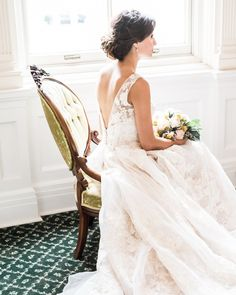 We love a dress that is stunning from all angles. The plunging back on Rachel's Oleg Cassini wedding dress contrasts the high-neckline and all is balanced with stunning lace and a full skirt. A soft updo and minimal accessories complete her romantic look. | Photo by Deborah Ann Photography via Borrowed & Blue