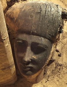 Encased in soil, this extraordinarily delicate face emerges into the sun for the first time in thousands of years.    The wooden sarcophagus was unearthed by archaeologists at the necropolis of Qubbet el-Hawa in Aswan, Egypt.    Believed to contain the body of a person of some rank, it boasts extraordinarily delicate features, well-preserved by the sands of time