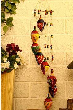 The multi cloured wind chime is hand painted with acrylic paints, the chimes being the seven Shankhs- a sacred Hindu object otherwise known in English as conch shells. Made in terracotta and arranged in layers.