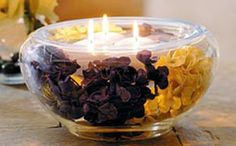 Centro de mesa con velas. Los colores fuertes de los pétalos de flores destacan las llamas de las velas