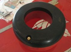 A black and red integral inflatable thread protector with some rulers are on the ground.