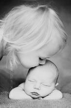 Schönes Erinnerungsfoto mit neugeborenem Baby und der großen Schwester