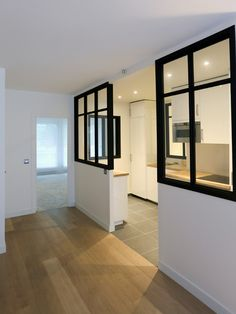 Cette cuisine blanche laquée est ouverte sur le salon. La lumière inonde la pièce grâce à une verrière sur-mesure. Le sol est recouvert d'un carrelage anthracite 60x60 cm et les murs sont peints en blanc. Dans le hall d'entrée et le salon, le sol est recouvert d'un parquet en chêne massif premier choix vernis blanc. - Xavier Lemoine Architecte d'Intérieur Paris -