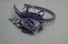 Tiara revestida em fita cetim lilás. com flor em tecido cetim, fitas e detalhes em miçangas prata. Para crianças a partir de 3 anos. R$ 12,00