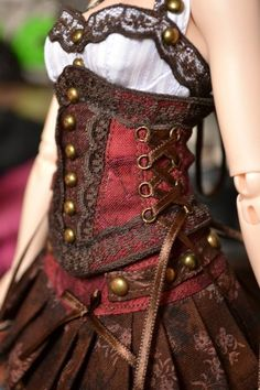 lovely steampunk burgundy red underbust corset with gold buttons and black braid and lace trim. Worn with a red and brown pleated skirt.