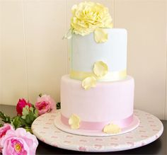 A deep, two tier wedding cake featuring a yellow flower as the cake topper. Shown here in pastel shades of yellow and pink, this wedding cake would suit a spring or summer wedding perfectly.