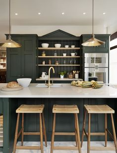 Hunter green kitchen cabinets with a brass sink faucet, pendant lights and hardware atop carrera marble counters.