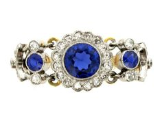 Belle Époque sapphire and diamond articulated ring, circa 1905. A yellow gold and platinum ring with articulated bezel horizontally set with three round old cut sapphires in platinum topped gold millegrain collet settings with an approximate total weight of 1.00 carats, the centre stone surrounded by a conforming single row of a sixteen round old cut diamonds in platinum topped gold millegrain collet settings, the flanking sapphires also set to top and bottom with two round old cut diamonds…