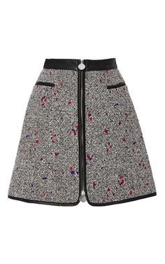 This **Carven** skirt is rendered in tweed and features an a-line shape with leather accents and a mini length hem.
