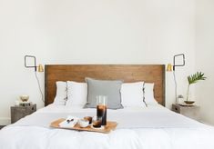 A plank wood headboard accents bed dressed in white bedding with black ribbon trim and a single gray flannel pillow flanked by black and gold swing-arm sconces over concrete block nightstands, CB2 Cement Gray Side Tables.