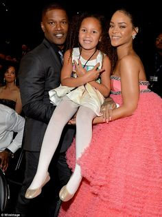 Peace out: Annalise flashed two peace signs while being supported by Rihanna and her father Jamie Foxx