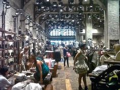 AllSaints store Michigan Ave., Chicago is one of the coolest stores you will ever visit! The interior space is designed to evoke the feel of an industrial European rail station. It touts a large glass atrium, flat iron black steel arches, and also 800 vintage sewing machines. The architecture and creative use of industrial equipment for displays are as interesting to look at as the hip clothing.