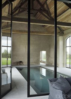 Inside A Streamlined Belgian Farmhouse - The poolhouse in a former barn features steel frames and original beams; the pool is sheathed with glass mosaic tiles, and the surround is Belgian bluestone.
