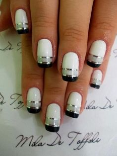 A black, gray and white ensemble creating a French tip separated by silver metallic strips for effect.