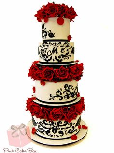 RED ROSE & BLACK DAMASK WEDDING CAKE This tiered cake has damask patterns with red roses separating each. It also bears the initial of the couple to personalize it.