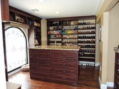 Custom walk in closet with slanted shoe shelves, handbag display and large double sided island.