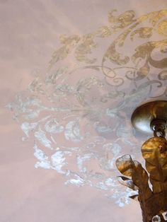 Metallic stencil on ceiling idea with a beautiful light fixture