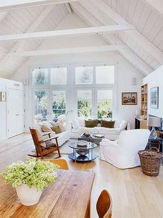 The hardwood floors and slipcovered sofas in this room are SO pretty. Love light, bright, and white!