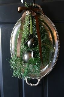 An old thrift store carving platter or handled tray, creamers, greens and a pretty ribbon make an eye catching wreath for your front door or over the fireplace.