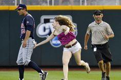 Una espectadora no identificada salta al campo de juego y le da unas palmaditas al jugador del Arizona Joey Rickard.