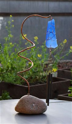 A freestanding Pacific beach stone wind chime- naturally beautiful. This wind chime has a large Pacific beach stone base. The copper support is embedded right into the stone base. The artist-made copp