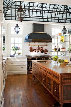 i bet those copper pots and pans are from williams sonoma...like $3,000 for a full set...dang it's lovely kitchen!