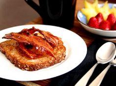 Receita de French toast com bacon e syrup - 4 fatias de pão gostoso, 1 ovo, 1/3 de xícara de leite, sal e um pouco de noz moscada, fatias de bacon, maple syrup (xarope de bordo) ou mel, óleo para fritar.