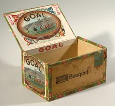 """""""Goal"""" football decorative cigar box c. 1900. Lidded mahogany box retaining a striking interior lid label having color lithographic football game scene titled """"Goal"""". Exterior of box is similarly titled along with matching end panel game scene labeling. 5"""" tall by 8"""" long having light general overall surface wear. """"3 for 5"""" written in period ink on end panel. $771"""