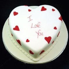 Torta Corazón decorada con fondant blanco y corazones rojos, mensaje central en tinta comestible