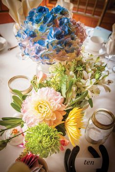 Can't see it under all those flowers, but there is an #AntiqueTeapot, an old cream bottle, #MasonJar w/candles & #HorseShoe #TableNumbers #OurWedding #Weddingbells english-country-garden-wedding
