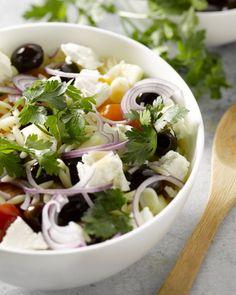 Orzo is een Griekse pastasoort die zich perfect leent voor salade. Zoals deze typische Griekse klassieker met kerstomaten, komkommer, rode ui, olijven en feta.