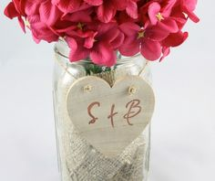 Simple wedding centerpiece featuring wooden heart embellishment with initials.