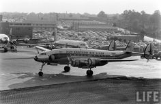 Eastern Air Lines N110A, a Lockheed L-749A Constellation, is followed by a DC-7 out to the active runway. This view faces west with the town of College Park in the distance.