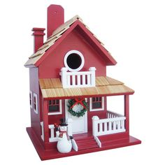 Invite feathered friends to roost in this festive birdhouse, showcasing a charming holiday cabin design.  Product: Birdhouse