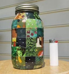 Quart-sized Mason Jar: Large Glass jar w/ Fabric - Green Patchwork via Etsy by Hercio Dias.  I think decoupaged with one inch paper squares would look great, too.
