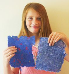 How to Make Beautiful Handmade Paper: Sam holds up handmade paper she made from recycled old paper, decorated with flower petals and leaves.