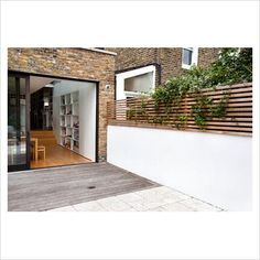 Bi fold floors leading from house to garden. Fence panel used to increase height of wall and add privacy.