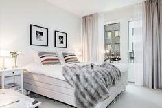 skandynawska sypialnia,aranżacja skandynawskiej sypialni,futrzana narzuta,futrzany szary pled,białe łóżko,poduszki w szaro-beżowe pasy,jak urządzić sypialnie skandynawską w nowoczesnym stylu