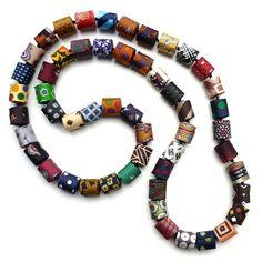 Perles roulottées en soie imprimée (cravates), lacet de coton ciré, longueur 110 cm. Rolled beads (printed silk from ties), cotton lace, length 110...